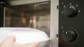 Una mano que saca un envase del horno de microondas