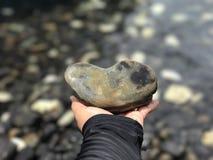 Una mano que soporta un corazón de la piedra fotografía de archivo libre de regalías