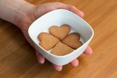 Una mano que sostiene el cuenco blanco con cuatro en forma de corazón Fotos de archivo