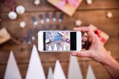 Una mano que sostiene el smartphone que exhibe la composición de la Navidad Imágenes de archivo libres de regalías