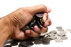 Una mano que sostiene muchas monedas en el fondo blanco aisladas Imagen de archivo libre de regalías