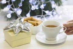 Una mano que sostiene una taza de té, un cuenco de galletas, una caja de regalo, árbol de navidad en la parte posterior Foto de archivo libre de regalías