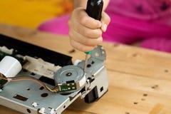 Una mano que sostiene un destornillador está instalando o está reparando Imágenes de archivo libres de regalías
