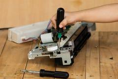 Una mano que sostiene un destornillador está instalando o está reparando Imagenes de archivo