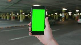 Una mano que sostiene un teléfono con una pantalla verde almacen de video