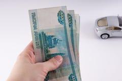 Una mano que sostiene una pila de mil notas de la rublo del dólar Cu ruso Imagen de archivo libre de regalías