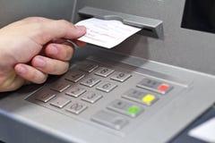 Una mano que toma un recibo de una máquina del cajero automático Fotografía de archivo libre de regalías