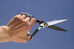 Una mano sosteniendo las tijeras Imagen de archivo