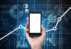 Una mano sostiene un smartphone con la pantalla blanca fotografía de archivo libre de regalías