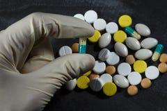 Una mano tiene una capsula sopra un mucchio delle pillole fotografia stock libera da diritti