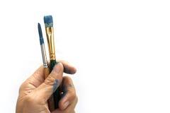 Una mano tiene le spazzole Fotografie Stock