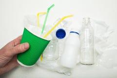 Una mano tiene una tazza di carta utilizzata su un fondo dell'immondizia riciclaggio immagini stock libere da diritti