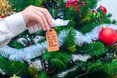 """Una mano tiene un'etichetta con un arco per un regalo """"non si apre fino al 25 dicembre """"sui precedenti dell'albero di Natale immagine stock libera da diritti"""