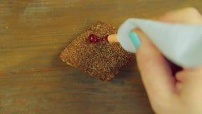 Una mano tiene un tubo di pittura culinaria ed estrae le tazze divertenti con pittura rossa sui biscotti di pepita di cioccolato  video d archivio