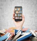 Una mano tiene uno smartphone con uno scaffale di libro sullo schermo Un mucchio dei libri colourful Un concetto di istruzione e  Fotografia Stock