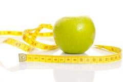 Una manzana con centímetro. Imagen de archivo libre de regalías