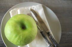 Una manzana con los cubiertos Imagen de archivo libre de regalías