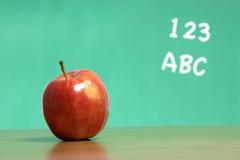 Una manzana en un escritorio en una sala de clase Fotografía de archivo