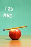 Una manzana en un escritorio en una sala de clase Imágenes de archivo libres de regalías