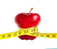 Una manzana flaca con una cinta de medición Imagen de archivo libre de regalías
