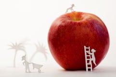 Una manzana roja grande con pequeños seres humanos de papel imagenes de archivo