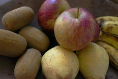 Una manzana roja orgánica real con otras frutas en una bandeja de madera foto de archivo