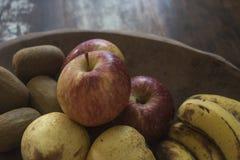 Una manzana roja orgánica real con otras frutas en una bandeja de madera sobre una tabla borrosa del grunge Imagen de archivo