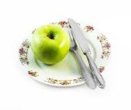 Una manzana verde con el cuchillo y bifurcación en una placa blanca con las decoraciones y el fondo blanco Imágenes de archivo libres de regalías