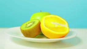 Una manzana verde entera y una mitad del kiwi y de la naranja en una placa blanca girar en un círculo almacen de metraje de vídeo