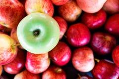 Una manzana verde entre el grupo de muchas manzanas rojas Imágenes de archivo libres de regalías