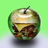 Una manzana y una hamburguesa Foto de archivo libre de regalías