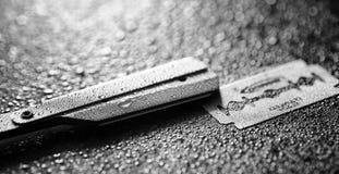 Una maquinilla de afeitar peligrosa y una cuchilla del metal en la tabla El afeitar del ` s de los hombres Fotos de archivo libres de regalías