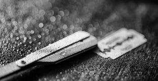 Una maquinilla de afeitar peligrosa y una cuchilla del metal en la tabla El afeitar del ` s de los hombres Imágenes de archivo libres de regalías