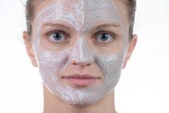 Una maschera di due cosmetici di argilla grigia con sfrega e screma sul fronte immagini stock libere da diritti