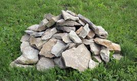 Una massa delle rocce sull'erba verde Fotografia Stock