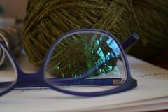 Una matassa di filato grigio è splesa attraverso gli occhiali di protezione blu scuro Immagine Stock