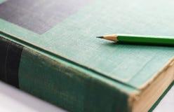 Una matita di legno verde è disposta sulla libro con copertina rigida o sul manuale Sel fotografia stock libera da diritti