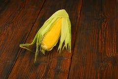 Una mazorca de maíz abierta en superficie de madera del vintage Foto de archivo