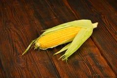 Una mazorca de maíz abierta en superficie de madera del vintage Imagen de archivo libre de regalías