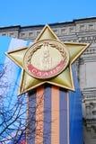 Una medaglia di gloria con un nastro dei colori arancio e neri Fotografie Stock