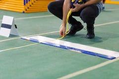 Una medida que toma oficial de la triple salto larga o Imagen de archivo
