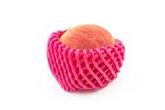Una mela con la rete di protezione della schiuma su fondo bianco isolato Fotografia Stock