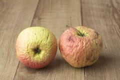 Una mela di due bruciature su fondo di legno Immagini Stock