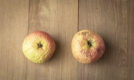 Una mela di due bruciature su fondo di legno Fotografia Stock