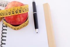 Una mela e un nastro di misurazione sul blocco note Immagini Stock Libere da Diritti