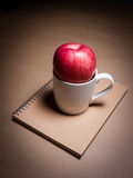 Una mela e una tazza su un taccuino marrone Immagine Stock Libera da Diritti