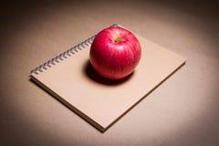 Una mela su un taccuino marrone Fotografia Stock