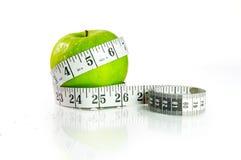 Una mela verde con nastro adesivo di misurazione Fotografia Stock