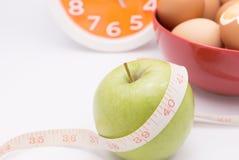 Una mela verde con nastro adesivo di misurazione lo ha avvolto per il co Immagine Stock Libera da Diritti
