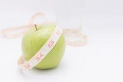 Una mela verde con nastro adesivo di misurazione lo ha avvolto per il co Fotografie Stock